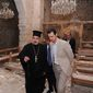 """In this photo taken on Sunday, April 20, 2014, and released on the official Facebook page of the Syrian Presidency, Syrian President Bashar Assad, right, checks a damaged church during his visit to the Christian village of Maaloula, near Damascus, Syria. Assad visited on Sunday a historic Christian village his forces recently captured from rebels, state media said, as the country's Greek Orthodox Patriarch vowed that Christians in the war-ravaged country """"will not submit and yield"""" to extremists. The rebels, including fighters from the al-Qaida-affiliated Nusra Front, took Maaloula several times late last year. (AP Photo/Syrian Presidency via Facebook)"""