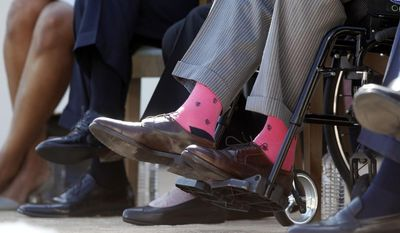 **FILE** Former President George H.W. Bush wears pink socks as he is seated in a wheelchair with, from left, first lady Michelle Obama, President Barack Obama, former first lady Barbara Bush, and former President George W. Bush, at the dedication of the George W. Bush presidential library on the campus of Southern Methodist University in Dallas, Thursday, April 25, 2013. (Associated Press)