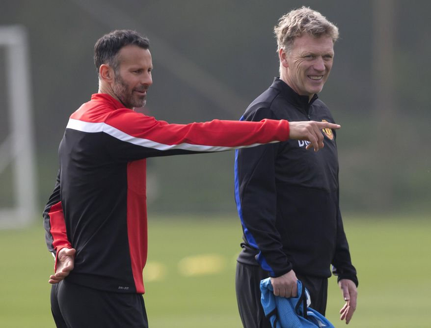 """FILE - In this Monday, March 31, 2014 file photo Manchester United's manager David Moyes, right, stands alongside Ryan Giggs as the team trains at Carrington training ground in Manchester. Manchester United says manager David Moyes has left the Premier League club after less than a year in charge, amid heavy speculation he was about to be fired. United released a brief statement in its website Tuesday, saying the club """"would like to place on record its thanks for the hard work, honesty and integrity he brought to the role."""" Giggs has been tipped to takeover on an interim basis. (AP Photo/Jon Super, File)"""
