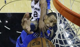 Dallas Mavericks' Monta Ellis, front, is fouled by San Antonio Spurs' Kawhi Leonard (2) as he tries to score during the first quarter of Game 1 of the opening-round NBA basketball playoff series, Sunday, April 20, 2014, in San Antonio. (AP Photo/Eric Gay)