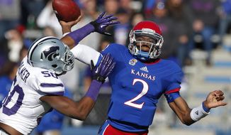 FILE - In this Nov. 30, 2013 file photo, Kansas quarterback Montell Cozart (2) passes over Kansas State linebacker Tre Walker (50) during the first half of an NCAA college football game in Lawrence, Kan. Cozart has won the starting job at Kansas, beating out Jake Heaps and T.J. Millweard after a strong spring game. (AP Photo/Orlin Wagner, File)