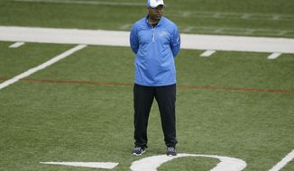 Detroit Lions head coach Jim Caldwell observes team drills at the Lions training facility in Allen Park, Mich., Tuesday, April 22, 2014. (AP Photo/Carlos Osorio)