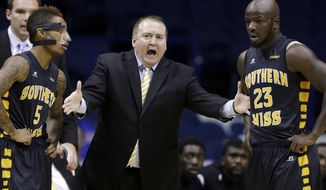 FILE - In this Nov. 13, 2013 file photo, Southern Mississippi head coach Donnie Tyndall, center, talks to guards Neil Watson, left, and Jerrold Brooks during the first half of an NCAA college basketball game against DePaul, in Rosemont, Ill. Tennessee is counting on Tyndall to make the same successful transition from the mid-major ranks as the Volunteers' last two men's basketball coaches. Tennessee announced Tuesday morning, April 22, 2014, that Tyndall would be introduced as its new coach at a 2 p.m. news conference. (AP Photo/Nam Y. Huh, File)