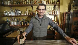 """In this April 16, 2014 photo, actor Ty Burrell, who plays bumbling dad Phil Dunphy on ABC's """"Modern Family,"""" poses holding a beer at Bar X, the cocktail bar he co-owns, in Salt Lake City. Burrell just opened Beer Bar, a beer garden-like eatery next door to Bar X that serves 150 beers paired up with an array of house-made bratwursts, local breads and Belgian fries. The restaurant sports long tables and benches with high ceilings to evoke that Bavarian beer hall feel. (AP Photo/Rick Bowmer)"""