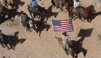 FILE - In this April 12, 2014, file photo, the Bundy family and their supporters fly the American flag as their cattle is released by the Bureau of Land Management back onto public land outside of Bunkerville, Nev.  The federal Bureau of Land Management says six cattle died in the roundup of animals it says rancher Cliven Bundy allowed to graze illegally on public land outside his southern Nevada property. The BLM said Tuesday, April 22, 2014, that two of four animals that were euthanized bore Bundy brands. (AP Photo/Las Vegas Review-Journal, Jason Bean, File) LOCAL TV OUT; LOCAL INTERNET OUT; LAS VEGAS SUN OUT