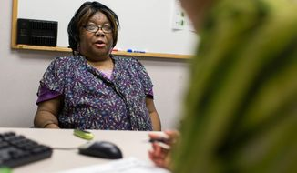 In this April 7, 2014 photo, Minneapolis resident Fannie Mae Anderson, who has diabetes, meets with nurse Carmelita Nelson at Hennepin County Medical Center in Minneapolis. Anderson has regular appointments with Nelson to help manage her diabetes, and she receives a bag of free nutritious food each time to help her eat healthier. (AP Photo/Minnesota Public Radio, Jennifer Simonson)
