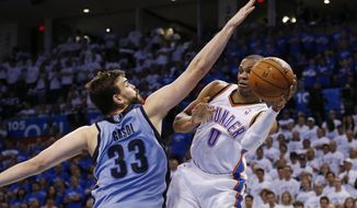Oklahoma City Thunder guard Russell Westbrook (0) passes around Memphis Grizzlies center Marc Gasol (33) in the fourth quarter of Game 2 of an opening-round NBA basketball playoff series in Oklahoma City, Monday, April 21, 2014. Memphis won 111-105 in overtime. (AP Photo/Sue Ogrocki)