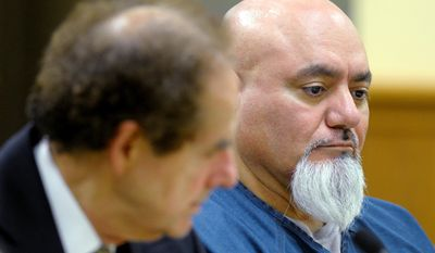 In this photo taken on Monday, April 21, 2014, Javier Garcia, right, listens during his sentencing in Kenosha, Wis. Garcia, convicted of strangling a woman in 2012 and leaving her body in a cemetery. was sentenced to life in prison, and a judge denied the possibility of parole after he continued to insist he was innocent. (AP Photo/The Kenosha News, Sean Krajacic)