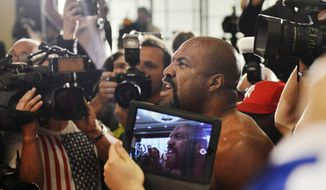 Former heavyweight world champion Shannon Briggs of the United States is surrounded by media as he shows up at a press conference of boxer Wladimir Klitschko of Ukraine ahead of Klitschko's  IBF, IBO, WBO and WBA heavyweight title bout against  challenger Alex Leapai from Australia-Samoa in Duesseldorf, Germany, April 22, 2014. Briggs demanded a title fight against Klitschko in the US. (AP Photo/Martin Meissner)