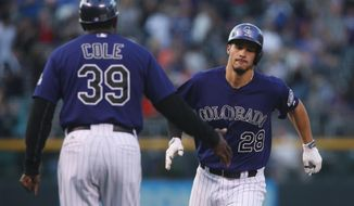 Colorado Rockies third base coach Stu Cole, left, congratulates Nolan Arenado as he circles the bases after hitting a solo home run against the San Francisco Giants in the first inning of a baseball game in Denver on Monday, April 21, 2014. (AP Photo/David Zalubowski)