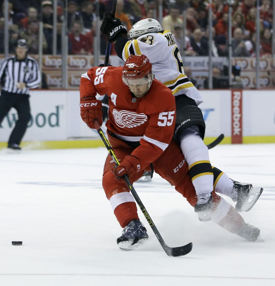 Boston Bruins left wing Brad Marchand (63) falls over Detroit Red Wings defenseman Niklas Kronwall (55) of Sweden as they chase the puck during the first period of Game 3 of a first-round NHL hockey playoff series in Detroit, Tuesday, April 22, 2014. (AP Photo/Carlos Osorio)