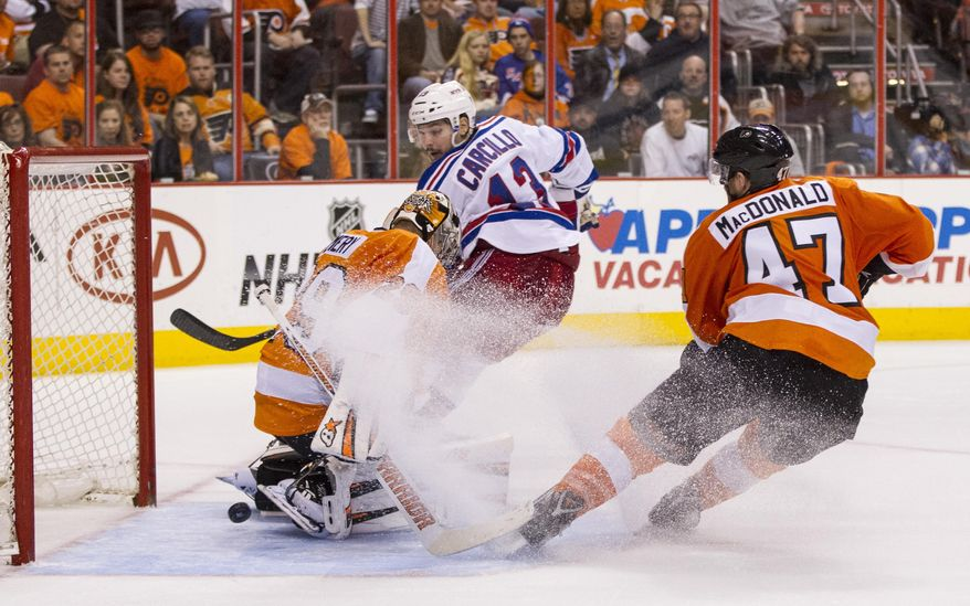 New York Rangers' Daniel Carcillo, center, watches his shot slip past Philadelphia Flyers' Ray Emery, left, for a goal with Andrew MacDonald, left, spaying some ice as he heads toward the goal during the third period in Game 3 of an NHL hockey first-round playoff series, Tuesday, April 22, 2014, in Philadelphia. The Rangers won 4-1. (AP Photo/Chris Szagola)