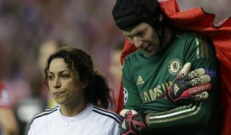 Chelsea goalkeeper Petr Cech holds his arm as he is covered by a blanket as he leaves the pitch following an injury during the Champions League semifinal first leg soccer match between Atletico Madrid and Chelsea at the Vicente Calderon stadium in Madrid, Spain, Tuesday, April 22, 2014 .(AP Photo/Paul White)