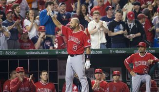 Los Angeles Angels' Albert Pujols (5) steps out of the visitors' dugout to acknowledge the applause from the crowd after hitting his career 500th home run, off Washington Nationals' Taylor Jordan in the fifth inning of a baseball game in Washington, Tuesday, April 22, 2014. (AP Photo/Pablo Martinez Monsivais)