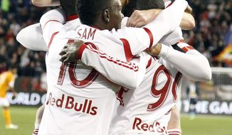 New York Red Bulls midfielder Dax McCarty, top, jumps on teammates while celebrating a goal by Bradley Wright-Phillips (99) against the Houston Dynamo during the first half of an MLS soccer game on Wednesday, April 23, 2014, in Harrison, N.J. (AP Photo/Julio Cortez)