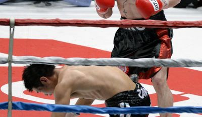 Spanish champion Kiko Martinez looks at Japanese challenger Hozumi Hasegawa kneeling down on the mat in the seventh round of their IBF super bantamweight boxing title bout in Osaka, western Japan, Wednesday, April 23, 2014. Martinez defended his title by technical knockout in the round. (AP Photo/Kyodo News) JAPAN OUT, CREDIT MANDATORY