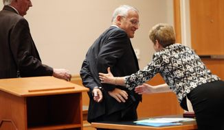 Monsignor Edward Arsenault reaches out with his handcuffed hand to shake hands with prosecutor Jane Young after pleading guilty to three felony theft charges in Hillsborough County Superior court in Manchester, N.H.m Wednesday April 23, 2014. Arsenault could spend to up to 20 years in prison for stealing at least $104,000 from a hospital, a dead priest's estate and the state's Roman Catholic bishop. (AP Photo/Jim Cole)