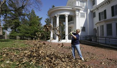 In this photo taken on Tuesday, April 22, 2014, volunteer Gloria Chaney, of Nebraska City, clears leaves from around the Morton Mansion, the former home of J. Sterling Morton who founded Arbor Day. The mansion is on the grounds of the Arbor Lodge State Historical Park and Arboretum in Nebraska City. People across the nation will observe Arbor Day on Friday, but no state will celebrate with as much fervor as Nebraska, where the celebration of trees got its start 142 years ago. (AP Photo/Nati Harnik)
