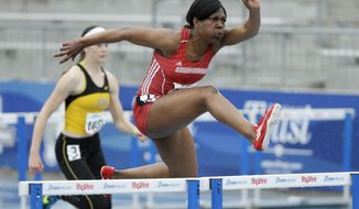 South Dakota's Tansha Clarke clears a hurdle in a heptathlon 100-meter hurdles heat at the Drake Relays athletics meet, Wednesday, April 23, 2014, in Des Moines, Iowa. (AP Photo/Charlie Neibergall)