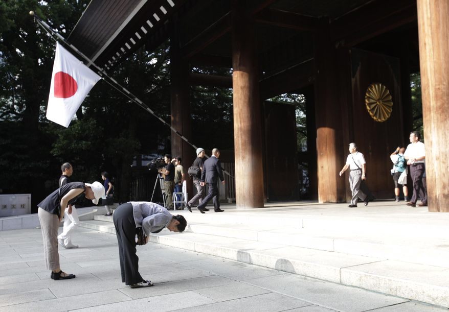 ** FILE ** In this Aug. 15, 2013, file photo, worshippers bow at Yasukuni Shrine in Tokyo. Justin Bieber has apologized to those he offended by visiting Japan's Yasukuni war shrine the week of April 20, 2014, saying he was misled to see it as only a place of prayer. (AP Photo/Shizuo Kambayashi, File)