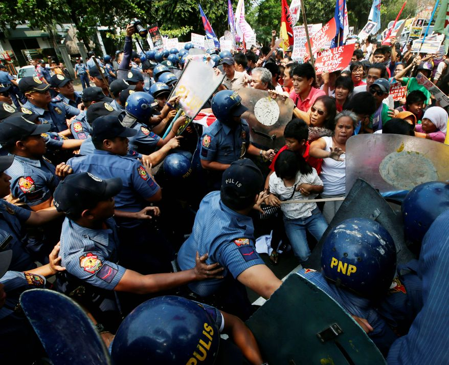 Policemen and protesters clash Wednesday in Manila as the latter try to force their way closer to the U.S. Embassy for a rally against next week's visit by President Obama. (associated press)