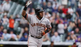 San Francisco Giants' Hector Sanchez celebrates after hitting a grand slam against the Colorado Rockies in the 11th inning of the Giants' 12-10 victory in 11 innings of a baseball game in Denver, Wednesday, April 23, 2014. (AP Photo/David Zalubowski)
