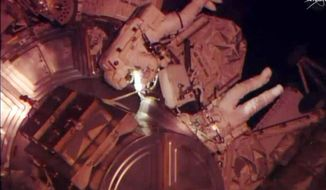 In this Wednesday, April 23, 2014 image made from video provided by NASA, astronauts Rick Mastracchio and Steven Swanson exit an airlock from the International Space Station. The spacewalk was scheduled to replace a dead computer and get their orbiting home back up to full strength. (AP Photo/NASA)