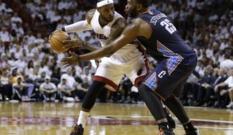 Charlotte Bobcats' Al Jefferson (25) defends Miami Heat's LeBron James during the first half in Game 2 of an opening-round NBA basketball playoff series, Wednesday, April 23, 2014, in Miami. (AP Photo/Lynne Sladky)