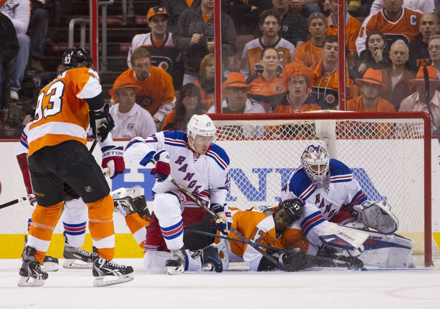 New York Rangers goalie Henrik Lundqvist, right, of Sweden, reaches for his stick next to teammate Ryan McDonagh, center left, and Philadelphia Flyers' Wayne Simmonds, center, who is sliding into Lundqvist during the third period in Game 3 of an NHL hockey first-round playoff series, Tuesday, April 22, 2014, in Philadelphia. The Rangers won 4-1. (AP Photo/Chris Szagola)
