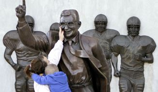 FILE - In this Oct. 8, 2010 file photo, Ashley Buchan holds her 4-year-old nephew Caleb Anthony, as she reaches to touch the face of the statue of former Penn State football coach Joe Paterno outside Beaver Stadium in State College, Pa. In 2012, the school removed this Paterno statue after a university-commissioned report accused the late coach and three other administrators of concealing sex abuse claims against retired assistant coach Jerry Sandusky. Fans of the late coach are commissioning a new statue to be placed across from the school at a local restaurant. (AP Photo/Keith Srakocic,File)