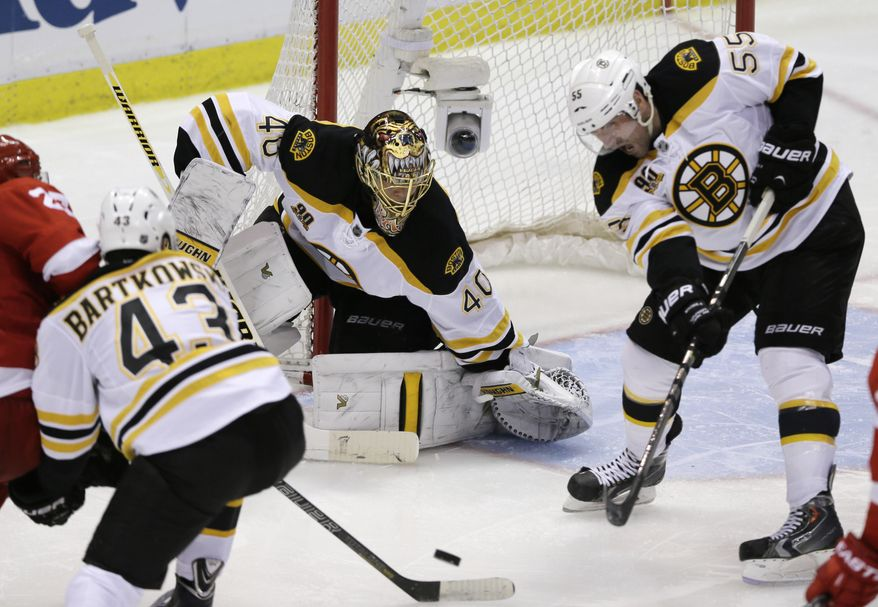 Boston Bruins defenseman Johnny Boychuk (55) helps keep the puck away from Boston Bruins goalie Tuukka Rask of Finland during the third period of Game 3 of a first-round NHL hockey playoff series against the Detroit Red Wings in Detroit, Tuesday, April 22, 2014. (AP Photo/Carlos Osorio)