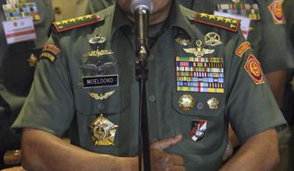 Wearing what he said to be a Chinese-made watch, Indonesian Armed Forces Chief Gen. Moeldoko speaks to the media during a press conference in Jakarta, Indonesia, Wednesday, April 23, 2014. Under fire in the media after being photographed with the luxury watch on his wrist, Indonesia's military commander says his critics should move on, explaining the timepiece is a cheap Chinese fake. (AP Photo)