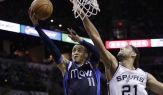 Dallas Mavericks' Monta Ellis (11) scores around San Antonio Spurs' Tim Duncan (21) during the second half of Game 2 of the opening-round NBA basketball playoff series on Wednesday, April 23, 2014, in San Antonio. Dallas won 113-92. (AP Photo/Eric Gay)