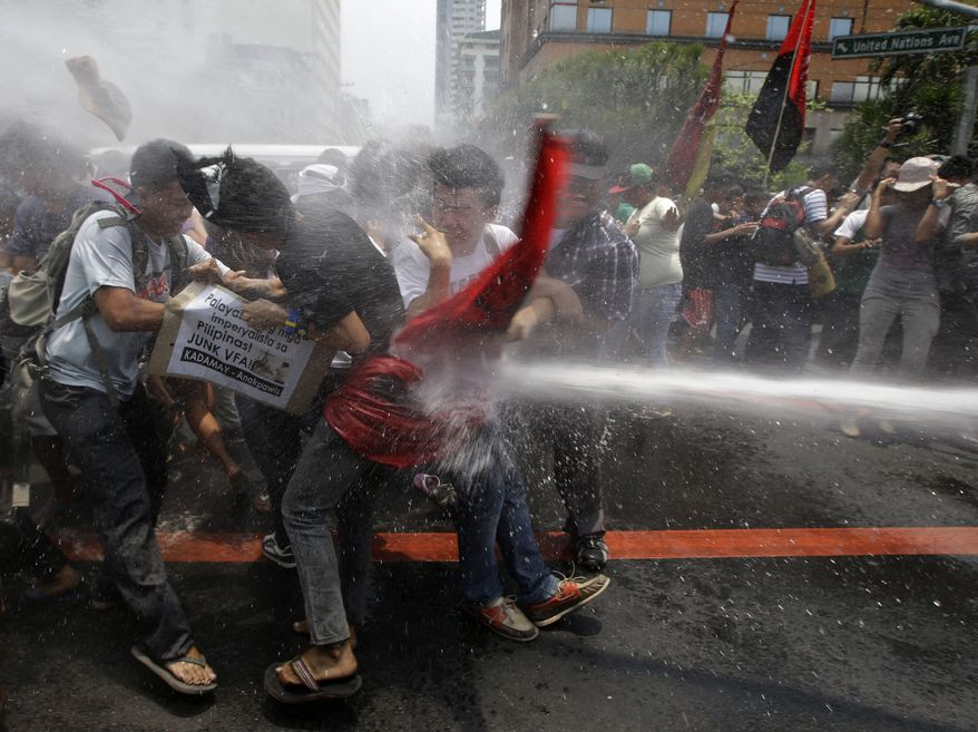 Police train their fire hose at protesters as the latter try to force their way closer to the U.S. Embassy for a rally against next week's visit of U.S. President Barack Obama, in Manila, Philippines, Wednesday, April 23, 2014. Philippine police armed with truncheon, shields and water hose have clashed with more than 100 left-wing activists who rallied at the U.S. Embassy in Manila to oppose a visit by Obama and a looming pact that will increase the American military presence in the Philippines. (AP Photo/Bullit Marquez)