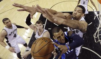 Dallas Mavericks' Monta Ellis (11) is pressured by San Antonio Spurs' Tim Duncan, right, as he tries to score during the first half of Game 2 of the opening-round NBA basketball playoff series on Wednesday, April 23, 2014, in San Antonio.  (AP Photo/Eric Gay)