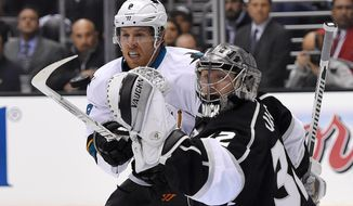 Los Angeles Kings goalie Jonathan Quick, right, is scored on by San Jose Sharks right wing Brent Burns as center Joe Pavelski looks on during the first period in Game 3 of an NHL hockey first-round playoff series , Tuesday, April 22, 2014, in Los Angeles. (AP Photo/Mark J. Terrill)