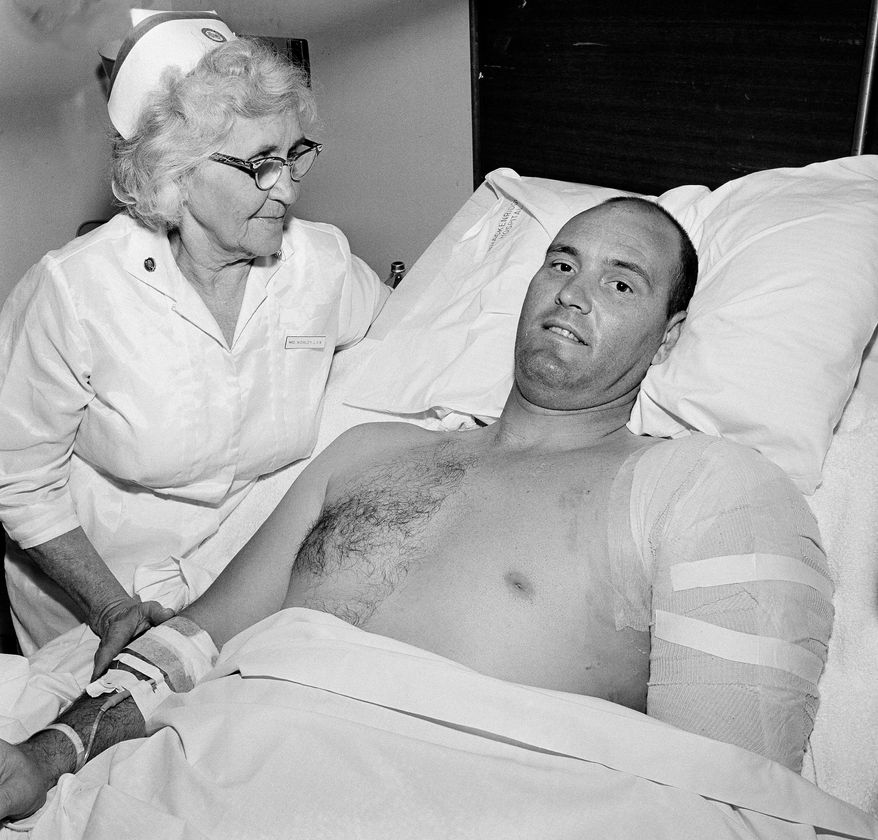 FILE - In this Aug. 3, 1966, file photo, Robert Heard, Associated Press staffer in Austin, Texas, is attended by his nurse, Annie Worley, at Brackenridge Hospital, where he is recovering from gunshot wounds suffered while he was covering a shooting spree at the University of Texas tower, in Austin. Heard, who reported on Texas state government, politics and sports for The Associated Press and a groundbreaking series on race and integration of Longhorns football, has died. He was 84. Heard died April 15, 2014, from complications after surgery to repair a broken hip, said widow Betsy Heard. (AP Photo/DO, File)