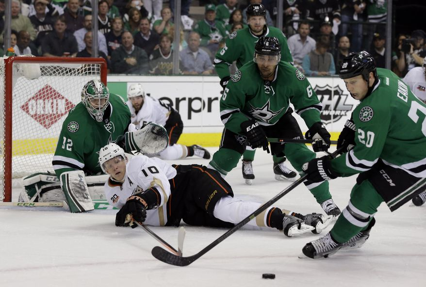 Anaheim Ducks' Corey Perry (10) has the puck stripped by the combined effort of Dallas Stars' Trevor Daley (6) and Cody Eakin (20) as goalie Kari Lehtonen (32), of Finland, watches in the second period of Game 4 of a first-round NHL hockey Stanley Cup playoff series, Wednesday, April 23, 2014, in Dallas. (AP Photo/Tony Gutierrez)
