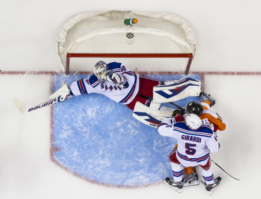 New York Rangers' Henrik Lundqvist, left, of Sweden stops a shot as teammate Dan Girardi (5) and Philadelphia Flyers' Scott Hartnell watch during the second period in Game 3 of an NHL hockey first-round playoff series, Tuesday, April 22, 2014, in Philadelphia. (AP Photo/Chris Szagola)