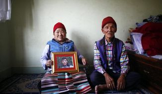 Nimdige Sherpa holds a portrait of her son Ang Kaji Sherpa, killed in an avalanche on Mount Everest, with her husband Ankchu Sherpa seated beside her in their rented apartment in Katmandu, Nepal, Wednesday, April 23, 2014. Dozens of Sherpa guides packed up their tents and left Mount Everest's base camp Wednesday, after the avalanche deaths of 16 of their colleagues exposed an undercurrent of resentment by Sherpas over their pay, treatment and benefits. (AP Photo/Niranjan Shrestha)
