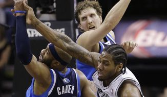San Antonio Spurs' Kawhi Leonard (2) is defended by Dallas Mavericks' Vince Carter (25) and Dirk Nowitzki, center, during the second half of Game 2 of the opening-round NBA basketball playoff series on Wednesday, April 23, 2014, in San Antonio. Dallas won 113-92. (AP Photo/Eric Gay)