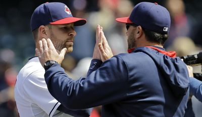 Cleveland Indians starting pitcher Corey Kluber, left, is greeted by pitching coach Mickey Callaway after a complete game, 5-1 win over the Kansas City Royals in a baseball game Thursday, April 24, 2014, in Cleveland. (AP Photo/Mark Duncan)