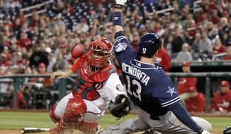 Washington Nationals catcher Jose Lobaton, left, is late with the tag on San Diego Padres' Chris Denorfia who is safe at home on a double hit by Seth Smith, during the fourth inning of a baseball game at Nationals Park, Thursday, April 24, 2014, in Washington. (AP Photo/Alex Brandon)