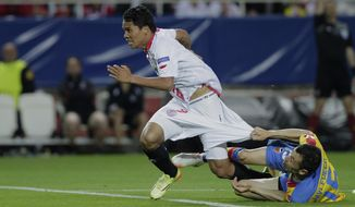 Sevilla's Carlos Bacca, left, and Valencia's Javi Fuego, right, fight for the ball during their Europa League semifinal first leg soccer match at the Ramon Sanchez Pizjuan stadium, in Seville, Spain on Thursday, April 24, 2014. (AP Photo/Miguel Angel Morenatti)