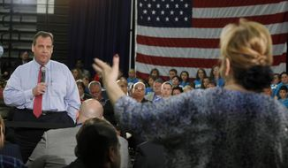 New Jersey Gov. Chris Christie listens to Carol Raab Davis of Toms River, during a town hall meeting in Brick Township, N.J., Thursday, April 24, 2014. Many questions at the town hall focused on the state's Sandy recovery efforts. (AP Photo/Mel Evans)
