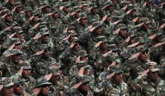 Protesting army soldiers salute as they sing their national anthem as they march through La Paz, Bolivia, Thursday, April 24, 2014. Hundreds of low ranking soldiers from Bolivia's Armed Forces marched for a third day against the military high command's dismissal of four of its leaders who defended their call for better career opportunities. Enlisted men are demanding changes so that non-commissioned officers in Bolivia's military may study to become career officers. (AP Photo/Juan Karita)