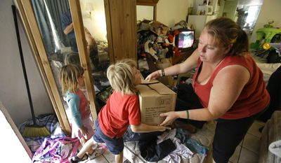 In this Tuesday, April 8, 2014 photo, Theresa Muller hands a box of times to her son Timothy, 7, with her daughter Mikenzie, 4, as she moves out of her motel room she shares with her boyfriend, father and three children in Kissimmee, Fla. Muller and her family have been homeless but plan to move to a home in a neighboring county.(AP Photo/John Raoux)