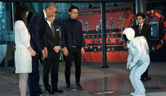 President Obama bows to a Japanese robot, ASIMO, during a youth science event at the National Museum of Emerging Science and Innovation in Tokyo.