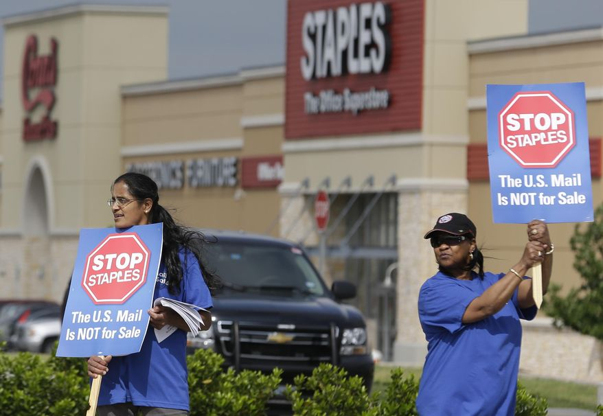 Postal worker Sophia Joseph, left, and retired postal worker Barbara Burkhalter hold signs outside a Staples store during a protest in Dallas, Thursday, April 24, 2014.  Thousands of postal workers around the nation are expected to picket outside Staples' stores to protest a pilot program of postal counters in the stores that are staffed with Staples employees. (AP Photo/LM Otero)