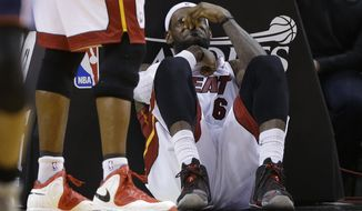 Miami Heat's LeBron James sits on the court after being elbowed by Charlotte Bobcats' Josh McRoberts during the second half in Game 2 of an opening-round NBA basketball playoff series, Wednesday, April 23, 2014, in Miami. The Heat defeated the Bobcats 101-97. (AP Photo/Lynne Sladky)